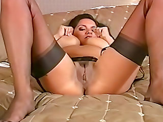 Busty brunette in nylon stockings is showing her kitty on the bed