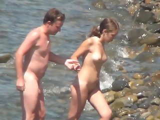 Goodly chick with gorgeous face and ideal ass is getting naked on the nudist beach