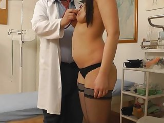 Perverted long-haired brunette is sitting in the medicine chair with spread legs