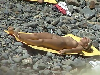 Beauty with natural tits is getting naked and lying on the sunny nudist beach