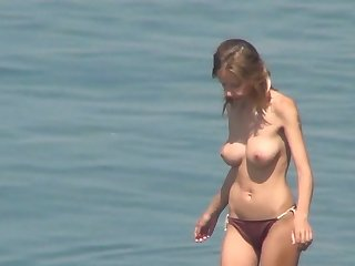 Sensual babe with natural boobies is swimming very sexy on the nudist beach in voyeur scene