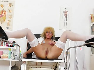 Cute-looking curly-haired blonde with trimmed pussy Patricie is sitting in the chair and playing with rubber dildo