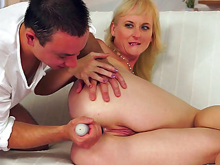 Sexy granny Monik is getting pounded in her tight asshole by that cocky dude on the couch