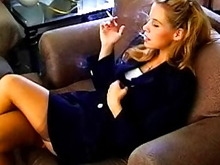 Her skirt suit combines with stockings to look beautiful and she smokes for your fetish.