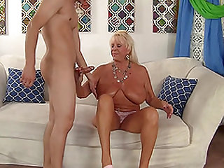 Mature blonde gives blowjob to a  guy