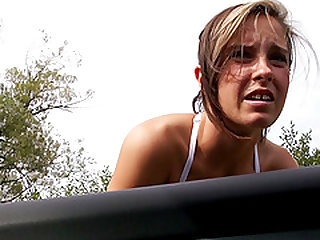 Little whore with chestnut hair sucks a dick in front of a car