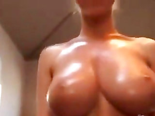 Naughty camgirl pours oil and bounces her huge rack