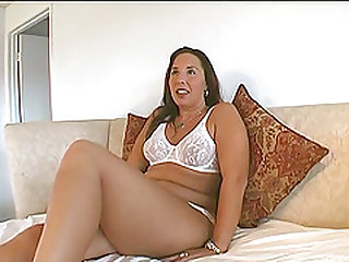 Chubby cougar with long dark hair playing with her shaved pussy